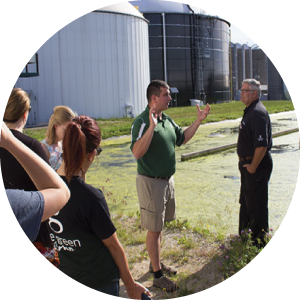 A photo of MSU employee Dana Kirk speaking to several students in front of the South Campus Anaerobic Digester.