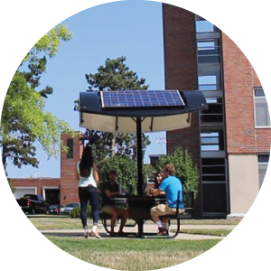 A photo of three students sitting around MSU's student solar table.