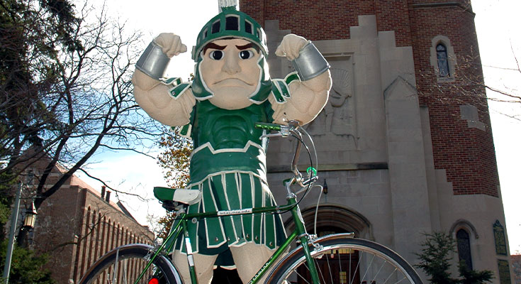 A photo of Sparty posing infront of Beaumont Tower with his bicycle.