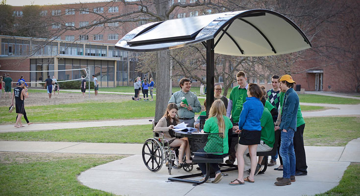 The student group, Sustainable Spartans, gather around the newly installed solar picnic table.