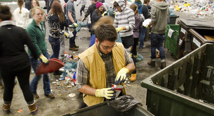 A student in gloves sorts waste into different containers.