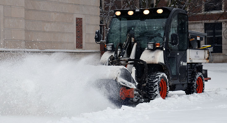 A photo of a Landscape Services employee operating snow broom equipment on a campus sidewalk.