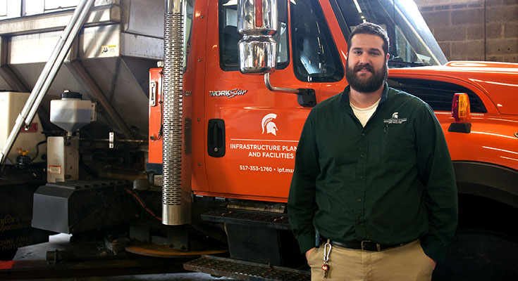A photo of Landscape Services Operations Supervisor Ross Weaver posing near some snow removal equipment.