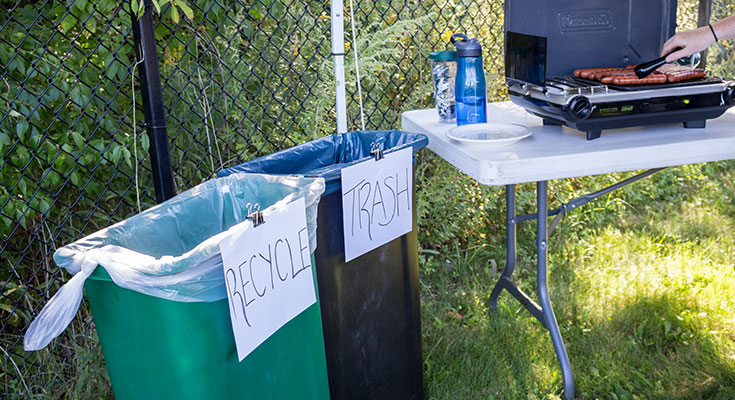 A photo of makeshift recycling containers at a tailgate.