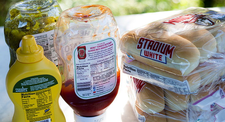 A photo of condiments and hot dog buns in bulk containers.