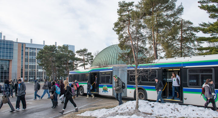 Students disembark from a CATA bus in the winter.