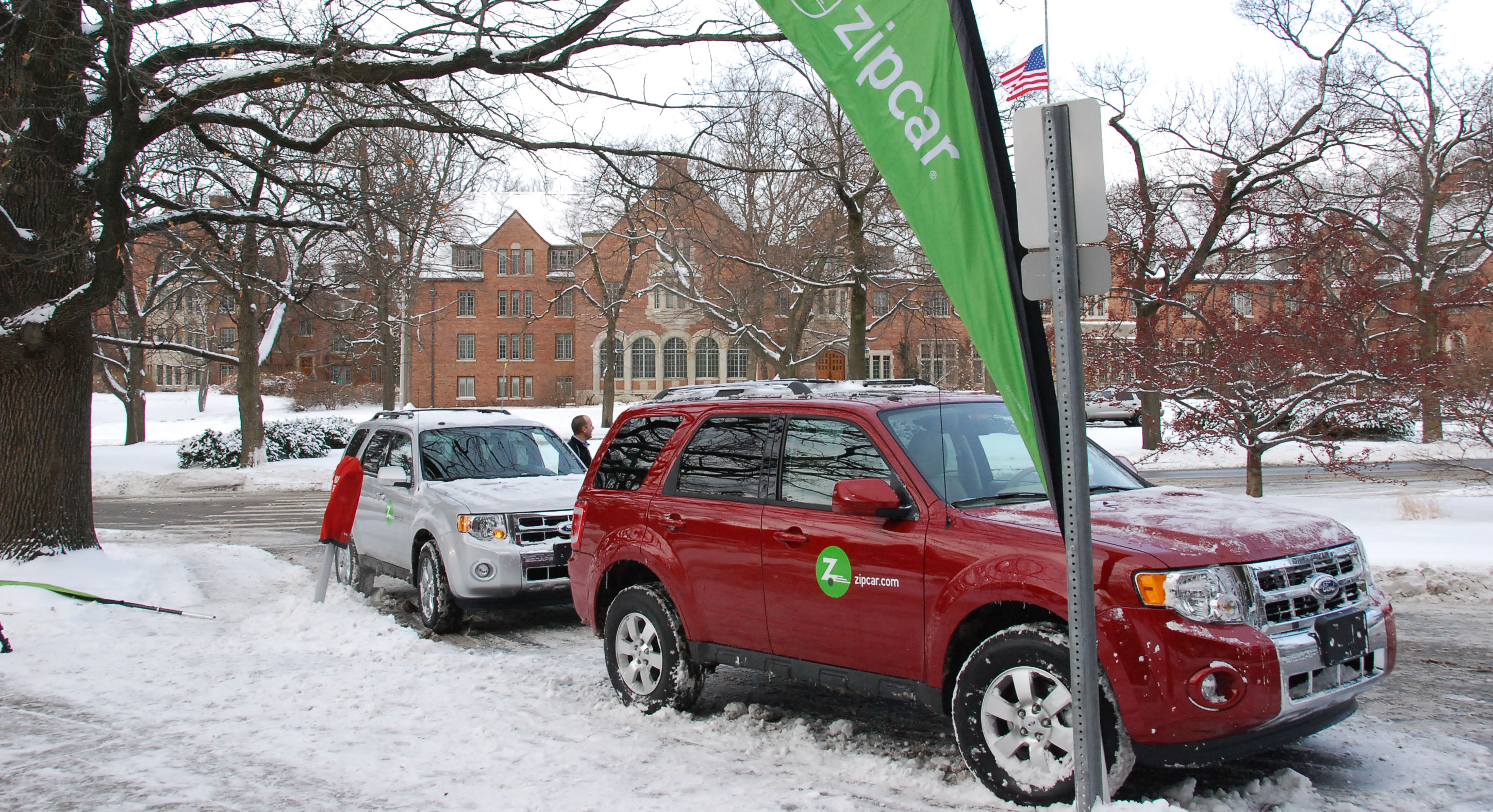 One white Ford Escape and one red Ford Escape are parked in front of the MSU Union by a Zipcar sign. Campus is snowy.
