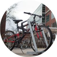 A photo of a red bike parked in a bike rack outside of Brody Hall.