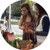 A photo of two women picking out fresh produce from the MSU Student Organic Farm Stand outside of the MSU Auditorium.